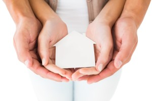 Couple holding miniature house in hands